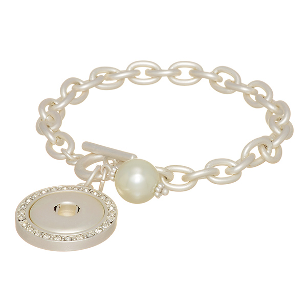 """Matte silver tone toggle bracelet featuring a faux ivory pearl and a rhinestone disk with a snap for snap-on charms. Snap jewelry collection. Approximately 7"""" in length."""
