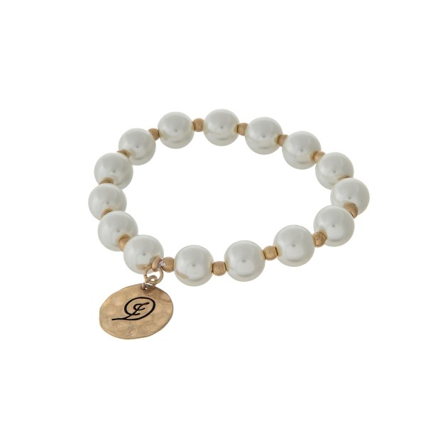 Gold tone stretch bracelet with cream pearl beads and a hammered disc stamped with a script 'D' initial.