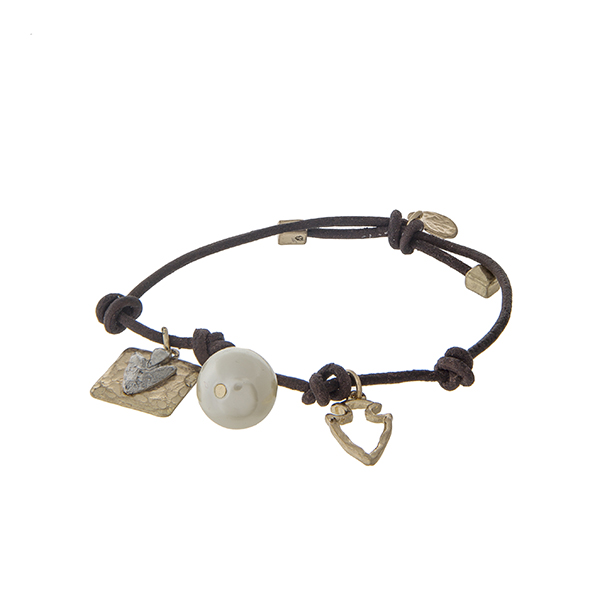 Brown leather cord adjustable bracelet with an arrowhead charm and a pearl bead.