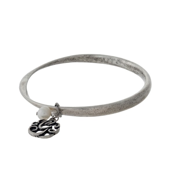 Burnished silver tone bangle bracelet with a script 'G' initial and freshwater pearl charm.