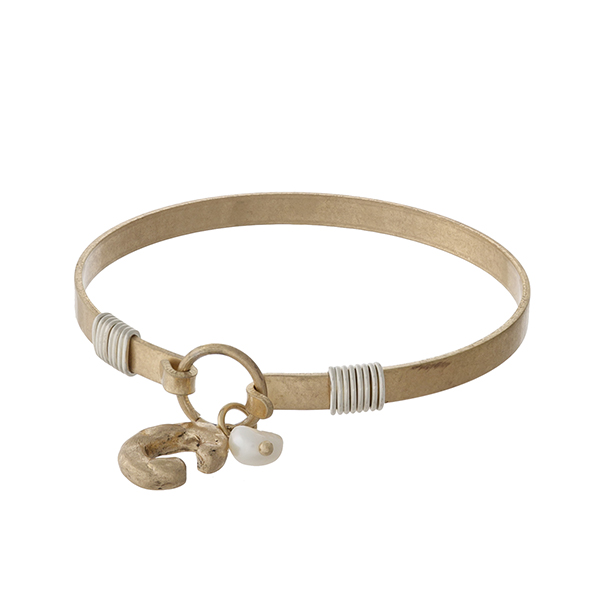 Gold tone bangle bracelet with a hook closure, a block 'C' charm, and a pearl bead accent.