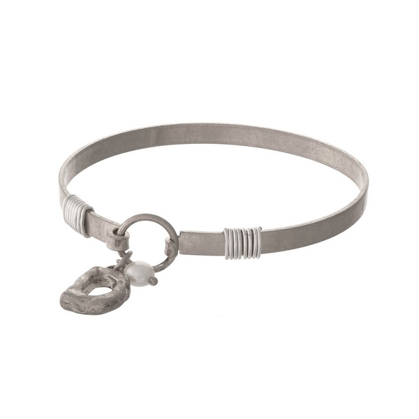 Silver tone bangle bracelet with a hook closure, a block 'D' charm, and a pearl bead accent.