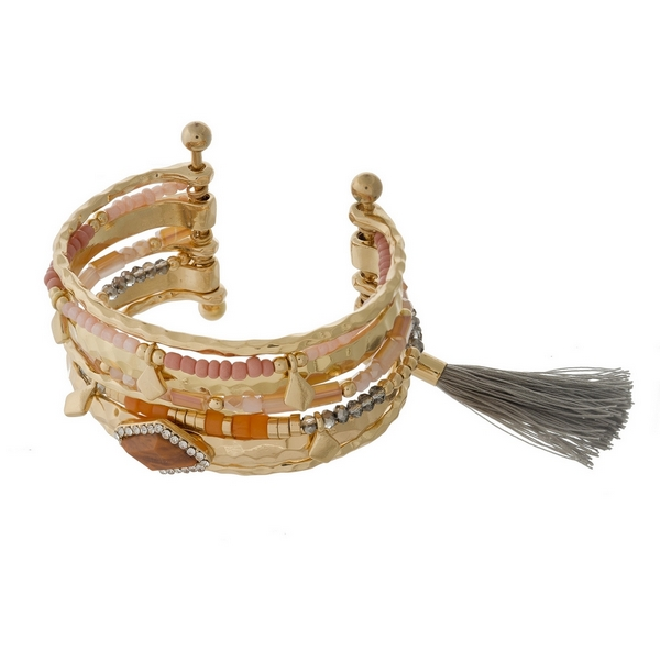 Hammered gold tone cuff bracelet with pink and coral beads and a black fabric tassel accent.