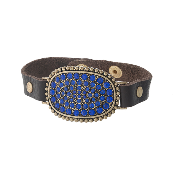 Brown leather snap bracelet with a gold tone focal, accented with blue rhinestones.