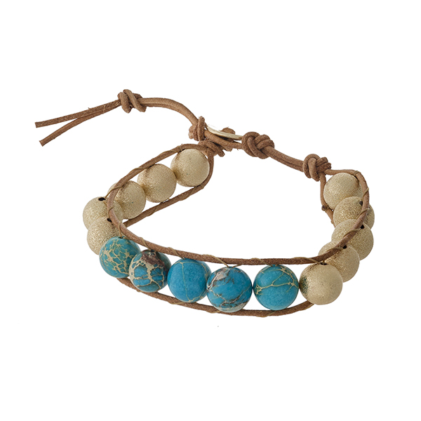 Brown cord bracelet with turquoise and gold tone beads and a button closure.