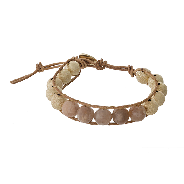 Brown cord bracelet with peach and gold tone beads and a button closure.