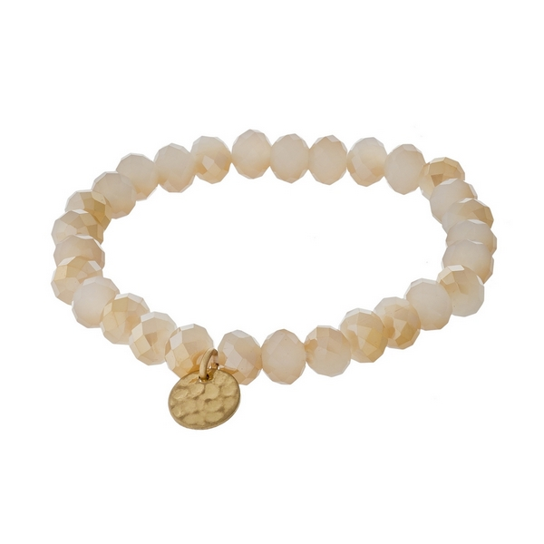 Ivory and champagne faceted bead stretch bracelet with a hammered gold tone circle charm.
