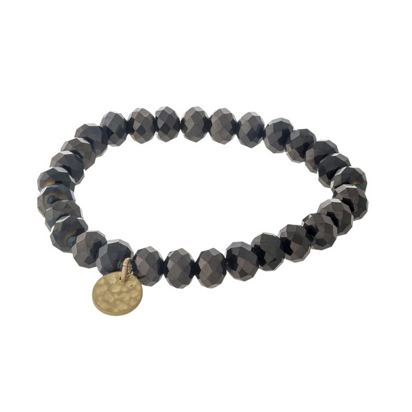 Hematite faceted bead stretch bracelet with a hammered gold tone circle charm.