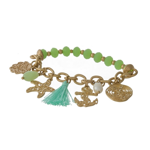 Gold tone and green beaded stretch bracelet displaying sealife and tassel charms.