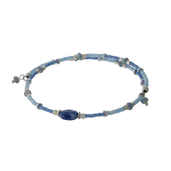 Dainty silver tone, wire bracelet with blue and light blue beads.