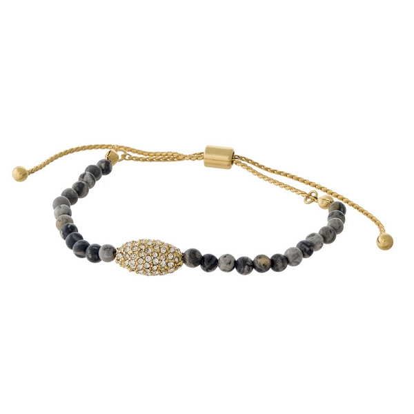 Gray beaded pull-tie bracelet with a gold tone and clear rhinestone pave focal.