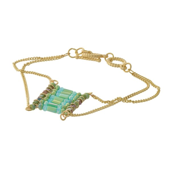 Gold tone toggle bracelet with a green beaded square focal.