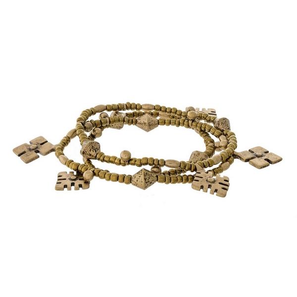 Gold tone three piece stretch bracelet set with bohemian charms.