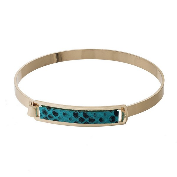 Gold tone bangle bracelet with a faux leather animal print focal and a hinge closure.