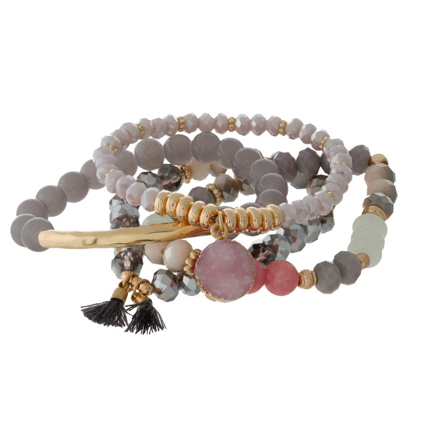 Four piece stretch beaded bracelet set with gold tone accents and a faux druzy stone charm.