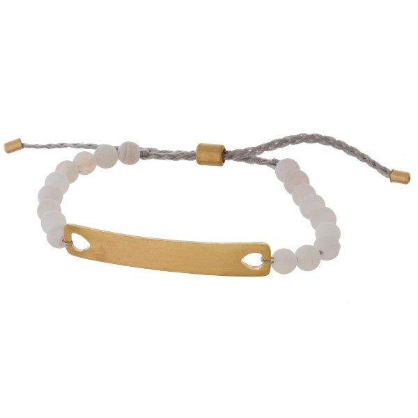 Dainty cord bracelet with a gold tone bar and natural stones.