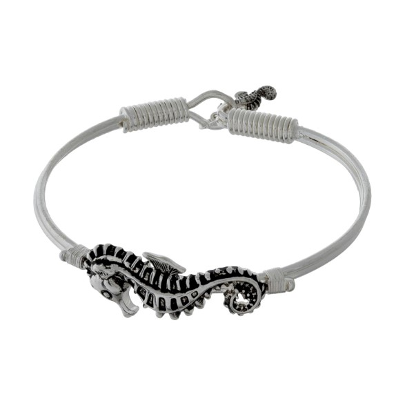 Silver tone bangle bracelet with a sea life focal and a hook closure.