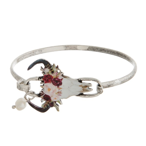 Burnished metal, bangle bracelet with a steer head and floral crown focal.