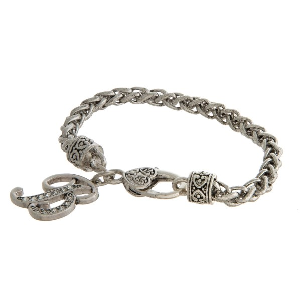Silver tone bracelet with a lobster closure and an initial charm.