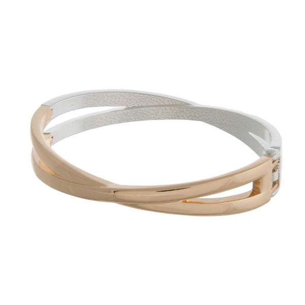 Silver and gold tone bangle bracelet with a hinge closure, and a twist design.