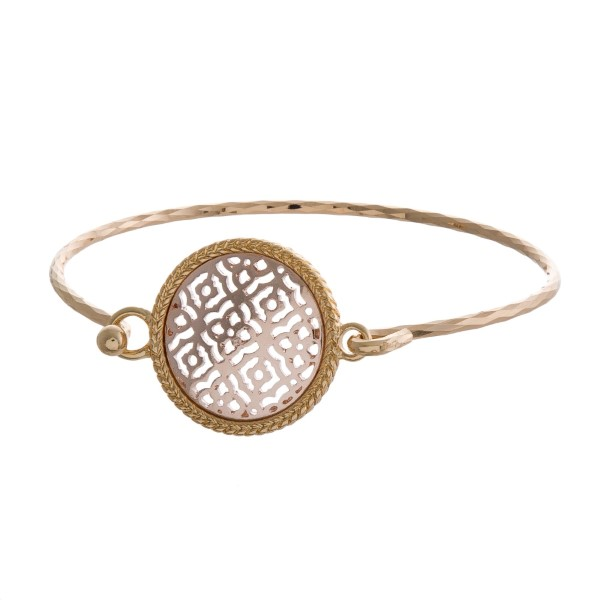 Gold tone bangle bracelet with a filigree, circle focal.