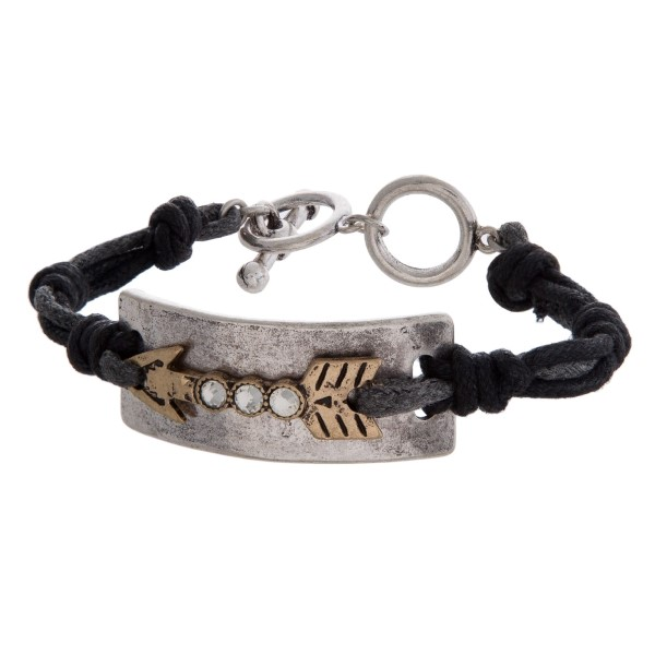 Cord bracelet with a two tone arrow focal and a toggle closure.
