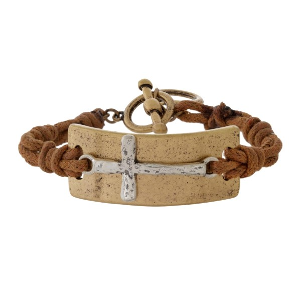Cord bracelet with a two tone cross focal and a toggle closure.