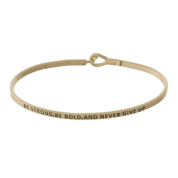 "Metal bracelet with engraved message, ""Be Strong, Be Bold, and Never Give Up."""