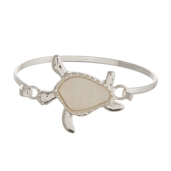 Metal, latch bracelet with a sea life focal accented with natural shell.