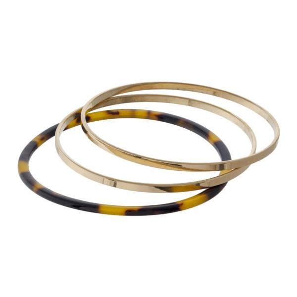 Gold tone metal and acetate bangles.