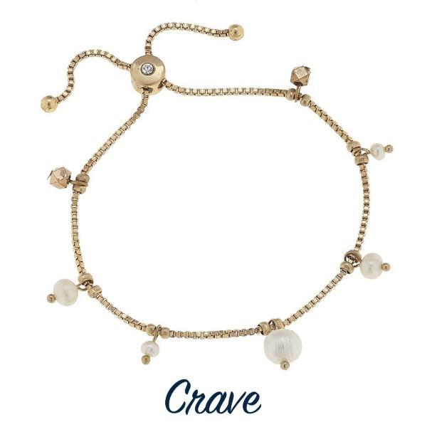 Adjustable metal bracelet with charm detail.