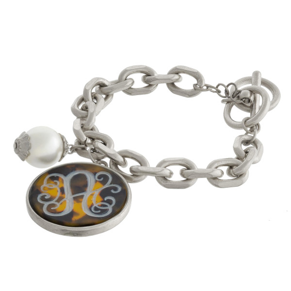 Metal chain bracelet with tortoise shell monogram charm and pearl detail.