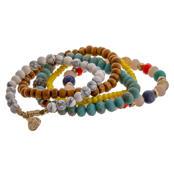 """Multicolor bracelet set featuring five beaded stretch bracelets with wood, iridescent, and natural stone inspired bead details with gold metal accents. Approximately 3"""" in diameter unstretched. Fits up to a 6"""" wrist."""