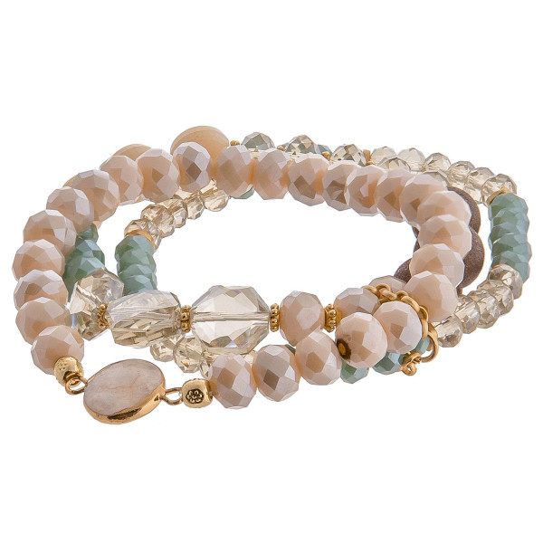 "Trio bracelet set featuring wood, iridescent and acrylic beaded details with a pearl accent. Approximately 3"" in diameter unstretched. Fits up to a 6"" wrist."