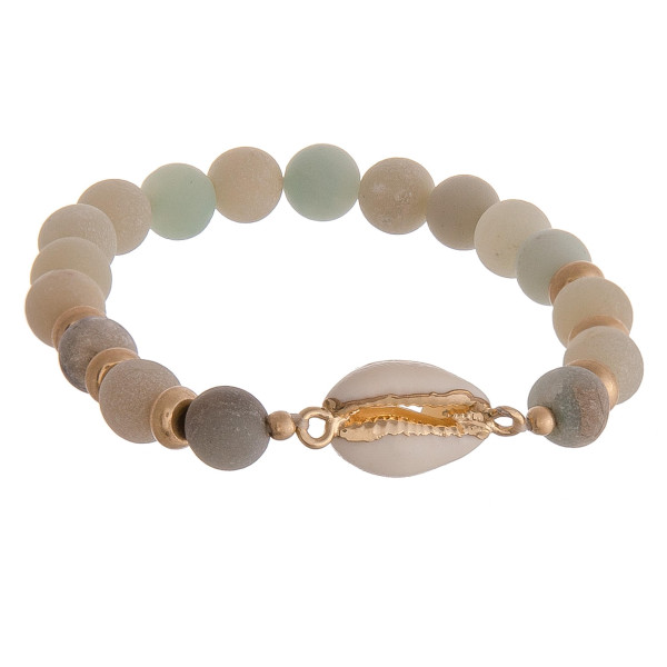 "Beaded stretch bracelet featuring mint natural stone inspired beads and a puka shell detail. Approximately 2.5"" in diameter unstretched. Fits up to a 5"" wrist."