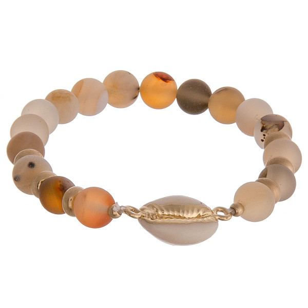 "Beaded stretch bracelet featuring natural stone inspired beads and a puka shell detail. Approximately 2.5"" in diameter unstretched. Fits up to a 5"" wrist."