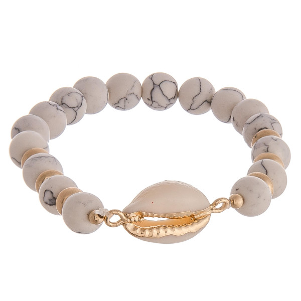 "Beaded stretch bracelet featuring white natural stone inspired beads and a puka shell detail. Approximately 2.5"" in diameter unstretched. Fits up to a 5"" wrist."