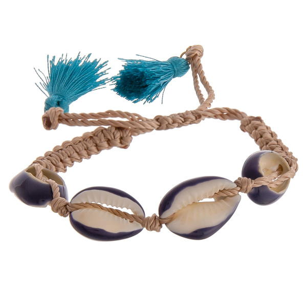 "Fabric bolo bracelet featuring Puka shell accents and fan tassel detailing. Approximately 3"" in diameter. Fits up to a 6"" wrist."