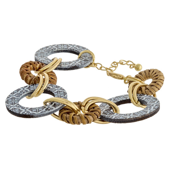 "Chain linked bracelet featuring rattan, metal, and wood accents. Approximately 2"" in diameter with a 1.5"" extender."