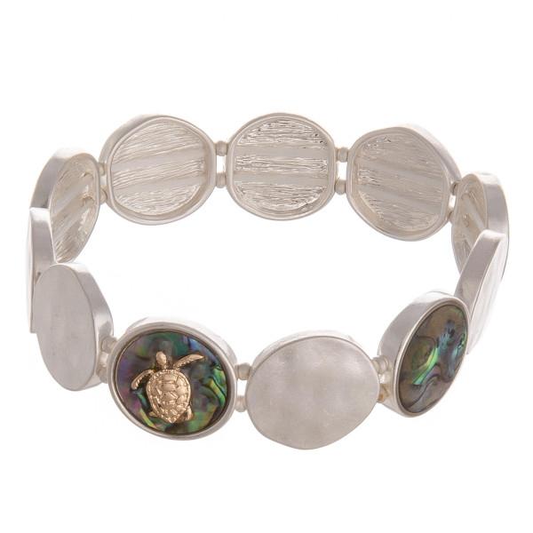 "Metal stretch bracelet featuring mother of pearl and a gold turtle detail. Approximately 2.5"" in diameter unstretched. Fits up to a 5"" wrist."