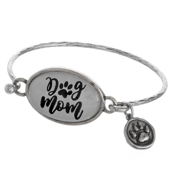 "Metal bangle bracelet featuring ""Dog Mom"" focal and a paw print charm. Approximately 2.5"" in diameter. Fits up to a 5"" wrist."