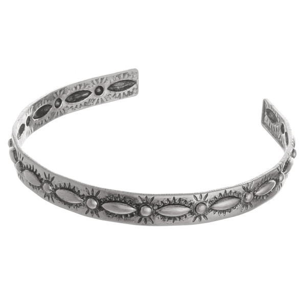 """Metal cuff bracelet featuring a flower inspired pattern. Approximately 2.5"""" in diameter. Fits up to a 5"""" wrist."""