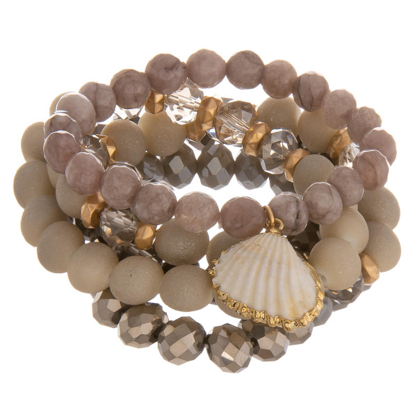 """Multi strand natural beaded bracelet with clamshell charm. Approximate 6"""" in length."""