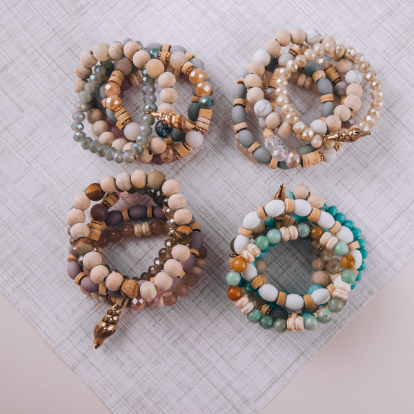 "Set of five beaded stretch bracelets featuring wood and natural stone beads with gold accents and a seashell charm. Approximately 2.75"" in diameter unstretched. Fits up to a 6"" wrist."
