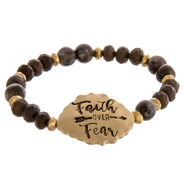 """Black beaded stretch bracelet featuring a gold accent engraved with the phrase """"Faith Over Fear."""" Approximately 2.5"""" in diameter unstretched. Fits up to a 6"""" wrist."""