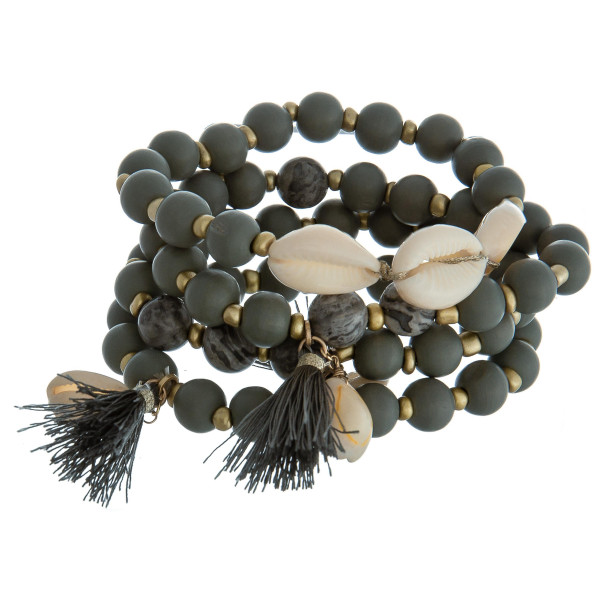 "Set of four beaded stretch bracelets featuring natural stone beads, puka seashells,  and tassel accents. Approximately 2.75"" in diameter. Fits up to 5"" wrist."