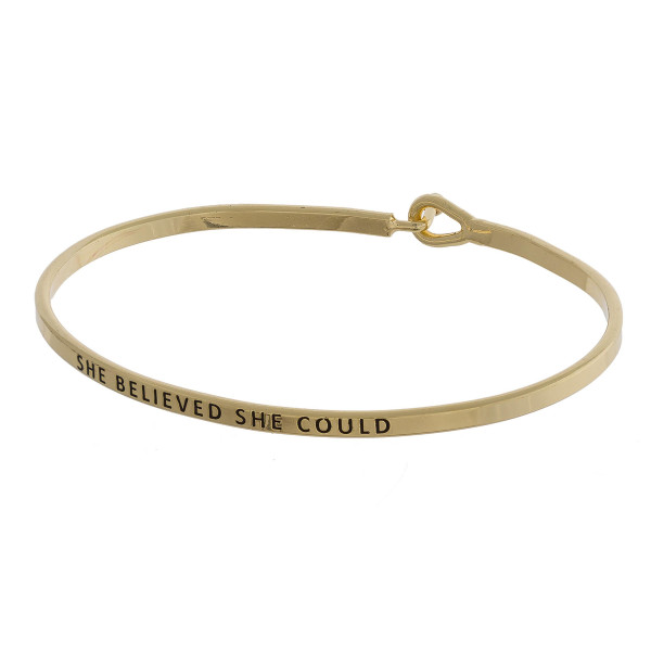 """Metal bracelet with engraved message, """"She Believed She Could."""" Approximate 2"""" in diameter."""