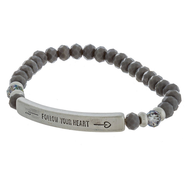 "Beaded stretch bracelet featuring a metal accent engraved with an arrow and the phrase ""Follow Your Heart"". Approximately 2.5"" in diameter unstretched. Fits up to a 6"" wrist."