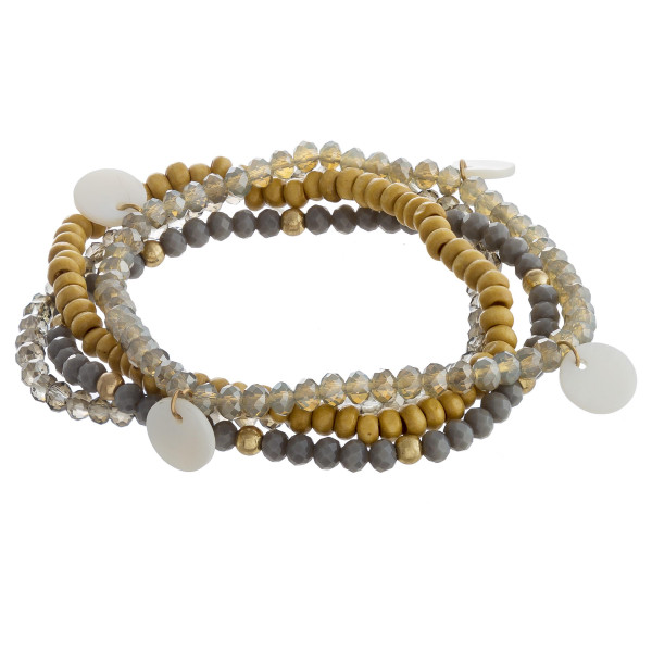 """Beaded bracelet set featuring four beaded bracelets with wood and faceted bead details and mother of pearl accents. Approximately 3"""" in diameter unstretched. Fits up to a 6"""" wrist."""