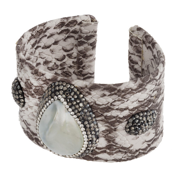 """Metal cuff bracelet featuring faux leather snakeskin and a gold accent. Approximately 2.5"""" in diameter. Fits up to a 5"""" wrist."""